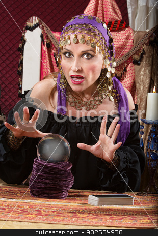 Caucasian Lady with Crystal Ball stock photo, Charming Caucasian woman in headscarf waving hands over crystal ball by Scott Griessel