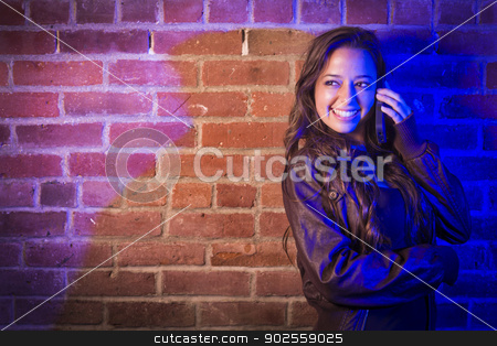 Mixed Race Woman Using Her Cell Phone Against Brick Wall stock photo, Portrait of a Pretty Mixed Race Young Adult Woman Using Her Cell Phone Against a Brick Wall with Plenty of Copy Space. by Andy Dean