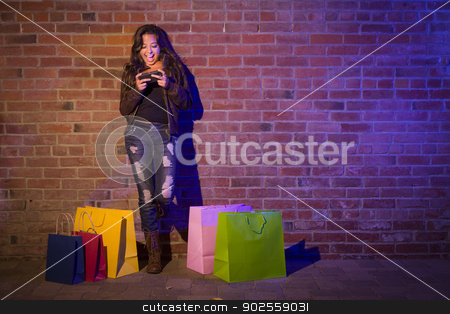 Woman with Shopping Bags Using Cell Phone Against Brick Wall stock photo, Pretty Mixed Race Young Adult Woman with Shopping Bags Using Her Cell Phone Against a Brick Wall - Plenty of Copy Space. by Andy Dean