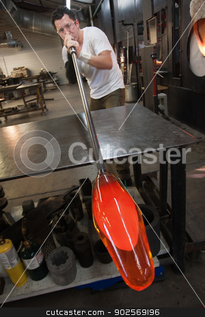 Man Blowing into Glass Object stock photo, Latino artist blowing into tube with molten glass object by Scott Griessel