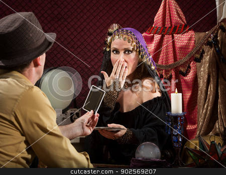 Shocked Fortune Teller stock photo, Attractive fortune teller covering her mouth with customer by Scott Griessel