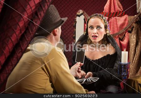 Man Shows Woman a Tarot Card stock photo, Businessman showing fortune teller his tarot card by Scott Griessel
