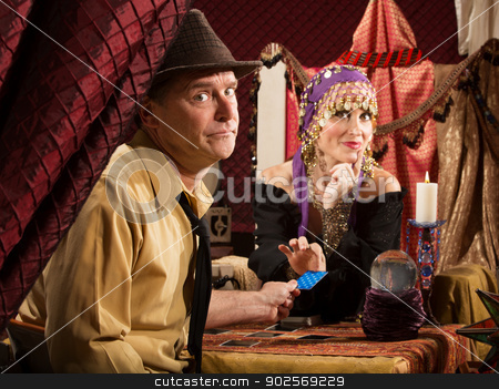 Fortune Teller Takes Credit Card stock photo, Beautiful fortune teller receiving payment from frowing man by Scott Griessel