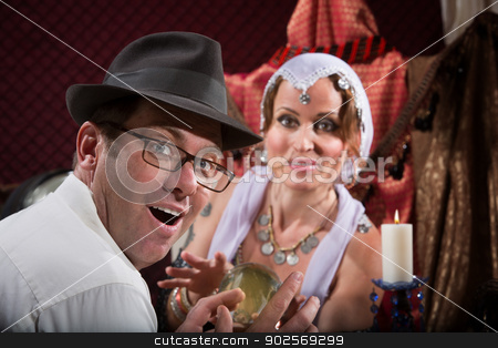 Lucky Man Gets His Fortune stock photo, Lucky male customer with happy gypsy holding crystal ball by Scott Griessel