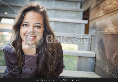 Mixed Race Young Adult Woman Portrait on Staircase stock photo, Portrait of a Pretty Mixed Race Young Adult Woman Sitting on a Staircase Wearing Leather Boots and Jacket. by Andy Dean