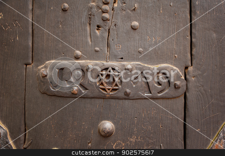 Metallic David star stock photo, Closeup of an door with Star of David into a steel frame placed on textured colorful old wood. by ifeelstock