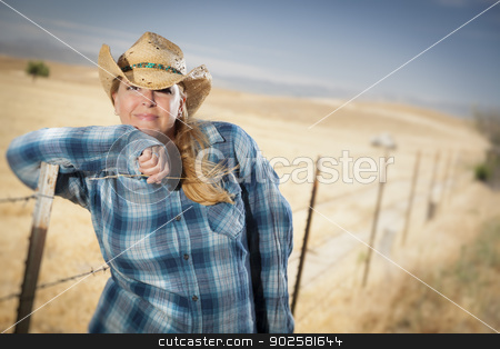 Beautiful Cowgirl Against Wire Fence in Field stock photo, Beautiful Cowgirl Against Barbed Wire Fence in Field. by Andy Dean
