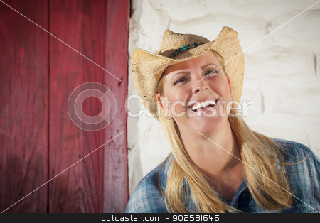 Beautiful Cowgirl Against Old Wall and Red Door stock photo, Beautiful Cowgirl Wearing Cowboy Hat Leaning Against Old Adobe Wall and Red Door. by Andy Dean