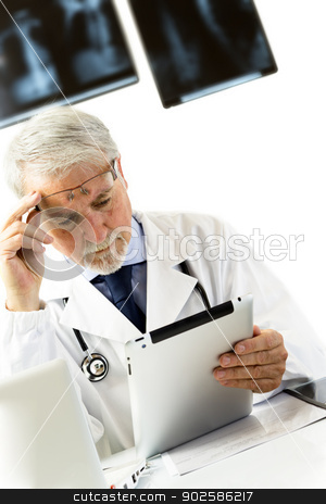 Doctor in clinic sitting at desk looking at x-rays on tablet stock photo, Doctor in clinic sitting at desk looking at x-rays on tablet, white background with x-rays. by Gianluca D'Auri Muscelli
