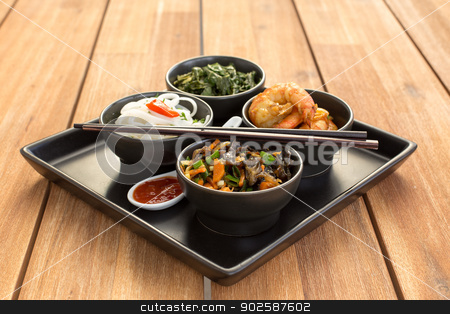 Traditional chinese dish stock photo, Traditional chinese dish on a square plate in black bowls with shrimp, rice noodles, kale (green cabbage) and fried vegetables. Composed with ceramic spoon with spicy red sauce and chinese chopsticks. Composition on a old styled wooden table. by doupix
