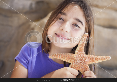Young Girl Playing with Starfish stock photo, Young Pretty Girl Playing with Starfish. by Andy Dean