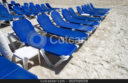 Blue Lounge Chairs stock photo, Rows of blue several lounge chairs on the beach by Kevin Tietz