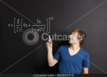 Young man pointing to a equation stock photo, Young man pointing to a equation on a chalkboard by ikostudio