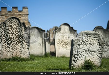 Old weathered gravestones stock photo, Old weathered gravestones arranged haphazardly on green grass, closeup view against a blue sky by Stephen Gibson