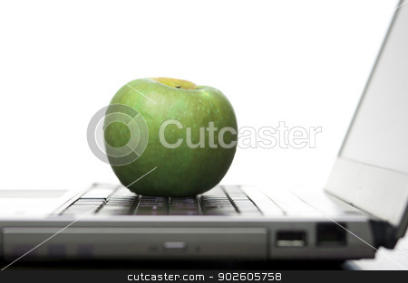 Green apple on an open laptop computer stock photo, Green apple resting on the keyboard of an open laptop computer in an education and healthy eating concept, low angle against a white background by Stephen Gibson