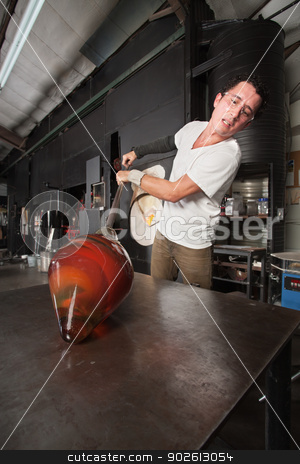 Man Shaping Glass Vase stock photo, Handsome glass artisan shaping beautiful glass vase on workbench by Scott Griessel