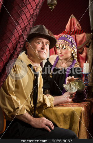 Fortune Teller Getting Paid stock photo, Disappointed man paying fortune teller cash money by Scott Griessel