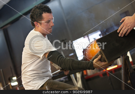 Glass Artist with Hot Vase stock photo, Handsome Latino glass artist holding steaming hot vase by Scott Griessel