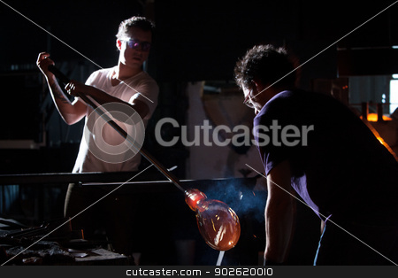 Making Glass in Dark Studio stock photo, Two men working with hot glass vase in dark studio by Scott Griessel