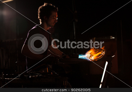 Person Shaping Glass with Blowtorch stock photo, Backlit man with blowtorch shaping glass object by Scott Griessel