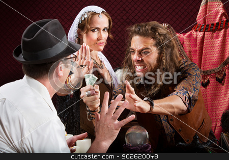Aggressive Fortune Tellers stock photo, Aggressive fortune tellers taking money from man in hat by Scott Griessel