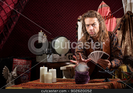 Man with Tarot  Cards stock photo, Male fortune teller with tarot cards waving hand over crystal ball by Scott Griessel