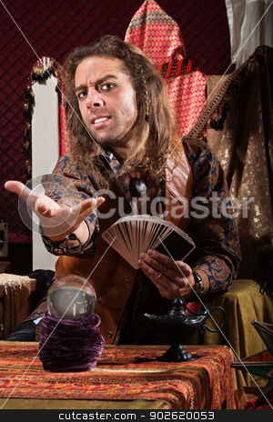 Fortune Teller Beckoning stock photo, Handsome male fortune teller with tarot cards and crystal ball by Scott Griessel