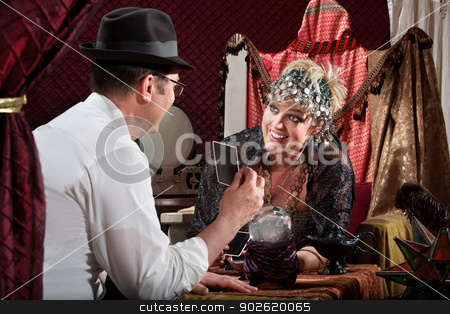 Female Gypsy Laughing at Customer stock photo, Laughing blond gypsy with customer holding tarot card by Scott Griessel
