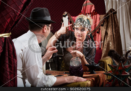 Lady Gesturing Bad Luck stock photo, Fortune teller gesturing a gun to her head with customer by Scott Griessel