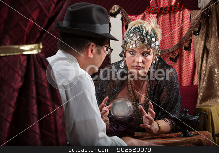 Serious Lady Fortune Teller stock photo, Grimacing lady fortune teller with customer and crystal ball by Scott Griessel
