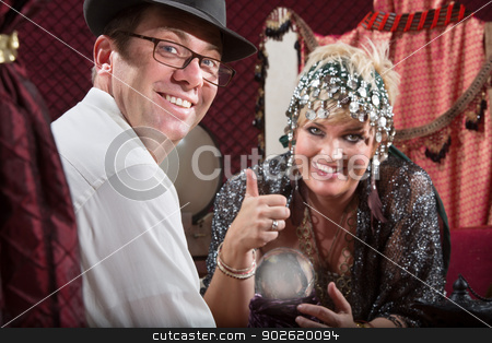Happy Customer and Fortune Teller stock photo, Happy fortune teller and customer with glowing crystal ball by Scott Griessel
