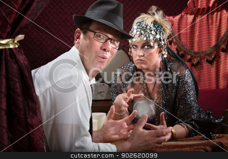 Excited Customer with Fortune Reader stock photo, Excited businessman and frowning woman with crystal ball by Scott Griessel