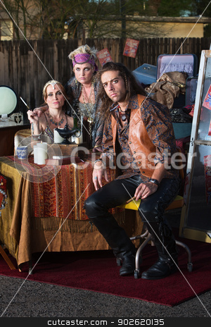 Fortune Tellers Kiosk stock photo, Handsome gypsy man sitting with female fortune tellers by Scott Griessel
