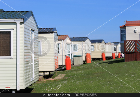 Row of caravans in trailer park stock photo, Row of caravans in trailer park, summer scene. by Martin Crowdy