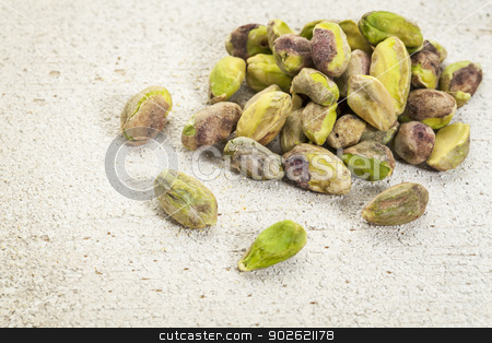 raw pistachio nuts  stock photo, a pile of raw pistachio nuts on a rough white painted barn wood background by Marek Uliasz