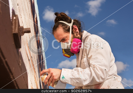 Man Spray Painting stock photo, Graffiti artist with respirator spray painting a wall by Scott Griessel