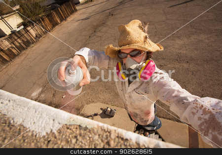 Graffiti Artist Defacing Wall stock photo, Graffiti artist in hat and sunglasses spray painting by Scott Griessel