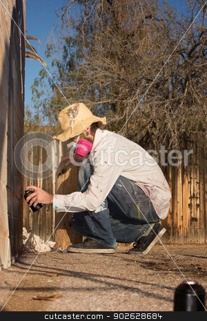 Crouching Man Spray Painting stock photo, Man crouching on the ground using spray paint on a wall by Scott Griessel