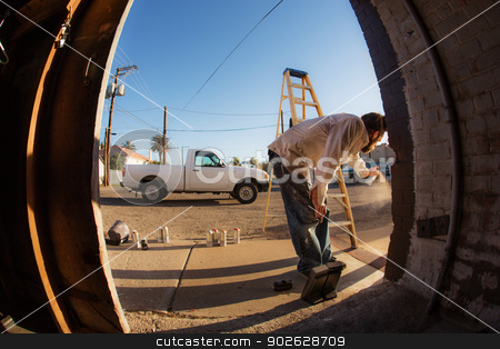 Male Graffiti Artist with Spray Cans stock photo, Wide angle view of man with spray paint cans and ladder by Scott Griessel