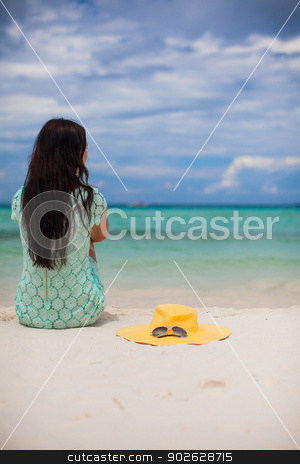 Back view of young fashion woman in dress on the beach and hat near her stock photo, Back view of young fashion woman in dress on the beach and hat near her by Dmitry Travnikov