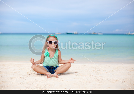 Beautiful little girl sitting in a lotus position on an exotic beach stock photo, Beautiful little girl sitting in a lotus position on an exotic beach by Dmitry Travnikov