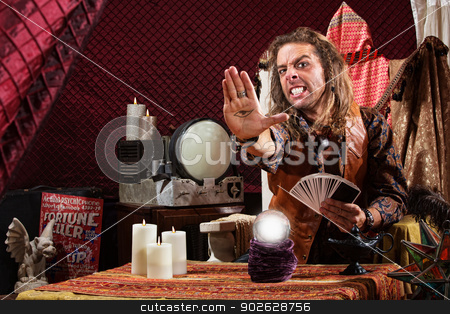 Tense Man with Evil Eye stock photo, Soothsayer with clenched teeth holding the evil eye in his palm by Scott Griessel