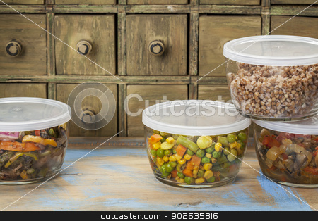 dinner leftovers stock photo, dinner leftovers (buckwheat kasha, vegetables, stir fry)  in glass  containers with drawer cabinet in background by Marek Uliasz