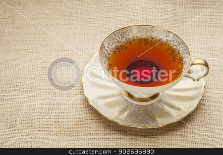 antique cup of tea stock photo, afternoon tea - antique cup of black tea on canvas  (burlap)background by Marek Uliasz