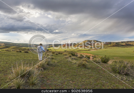 hiker and Red Mountain stock photo, male hiker with a backpack contemplates sunset over Red Mountain Open Space near Fort Collins, spring scenery by Marek Uliasz