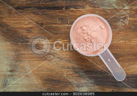 pomegranate fruit powder stock photo, measuring scoop of pomegranate fruit powder - top view against painted wood background by Marek Uliasz