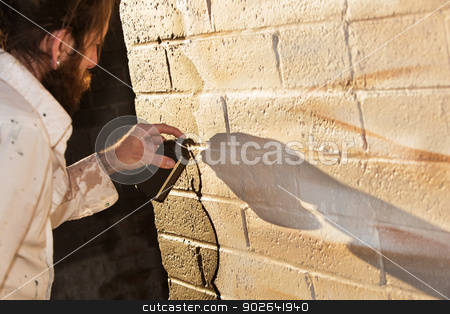 Mural Art with Spray Paint stock photo, Caucasian graffit artist working on mural with spray paint by Scott Griessel