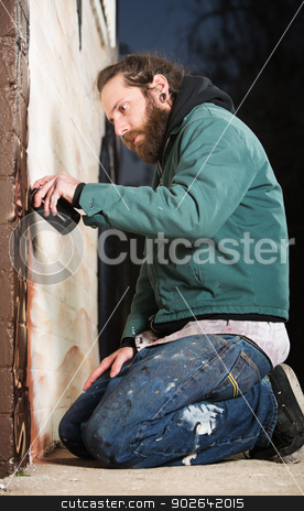 Kneeling Man Spray Painting stock photo, Man kneeling on the ground while spray painting a wall by Scott Griessel