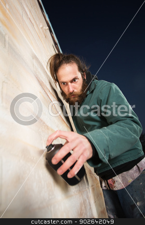 Serious Bearded Man Spray Painting stock photo, Serious man with beard spray painting a wall by Scott Griessel