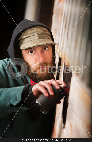 Sneaky Vandal Spray Painting stock photo, Sneaky vandal spray painting a wall outdoors by Scott Griessel